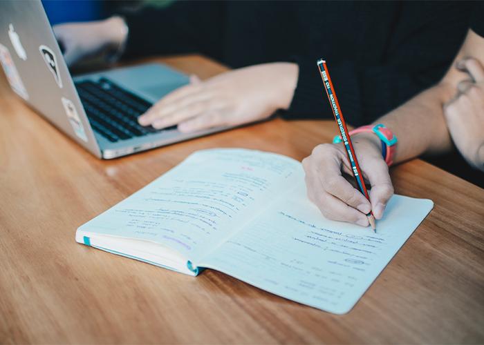 パソコンで作業する人と、ノートにメモを書き込む人の手元